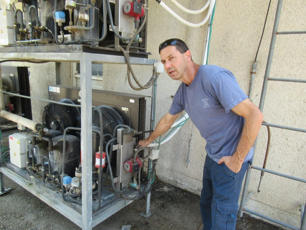 אבי אהוביה מצביע על מחליף החום שמנצל את אנרגיית הקירור גם לחימום מים