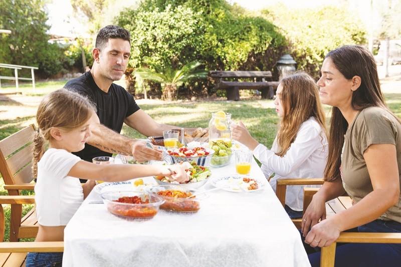 גיל ורויטל סלוקי ובנותהם בחצר המשק עם מעדני השף
