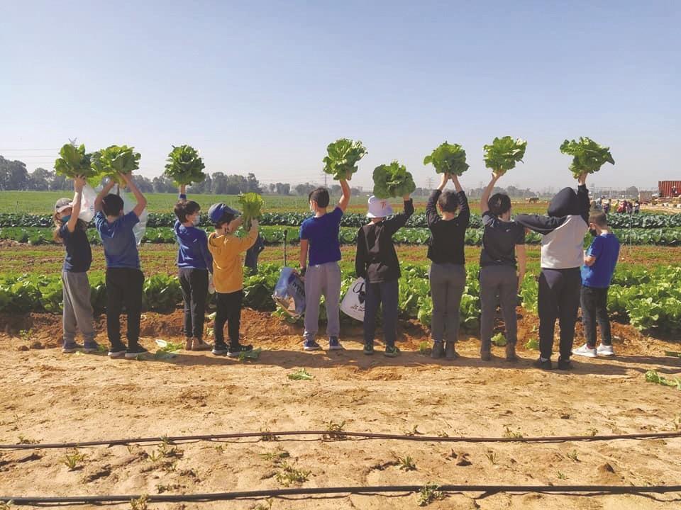 ילדים גאים בתוצרת בחווה החקלאית