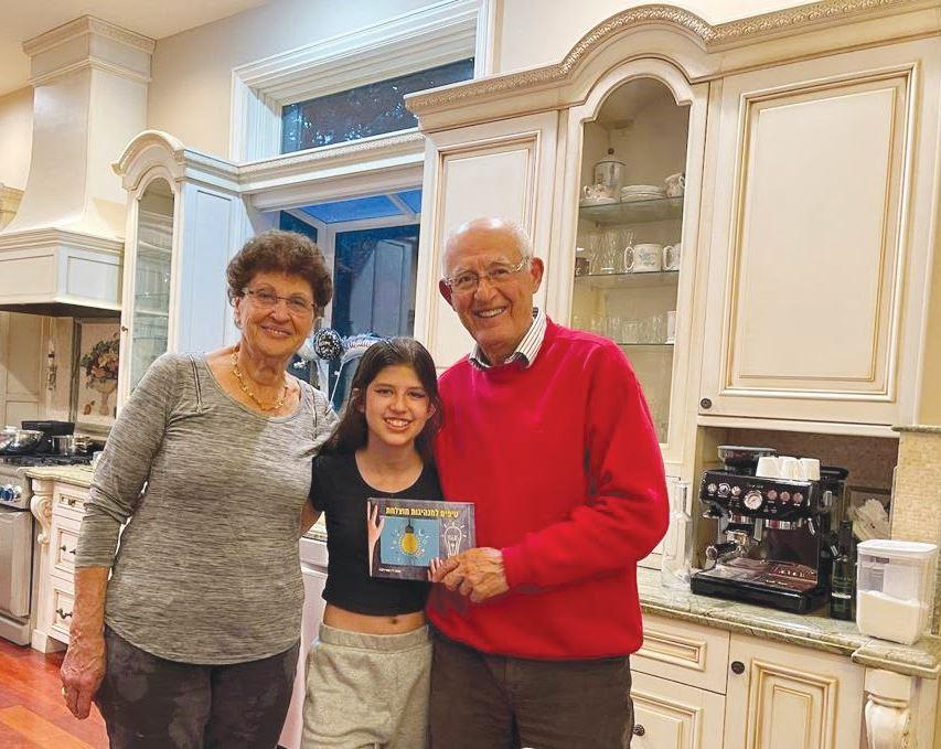 דוקטור מוטי דלגו רעייתו והנכדה מאיה מחזיק ביד את ספרו טיפים למנהיגות מוצלחת