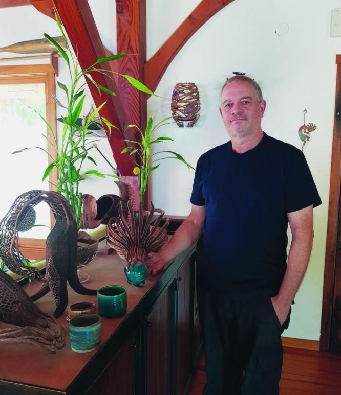 האמן אלישע רובינוף מהמושב השיתופי תימורים עם שלל העבודות שלו